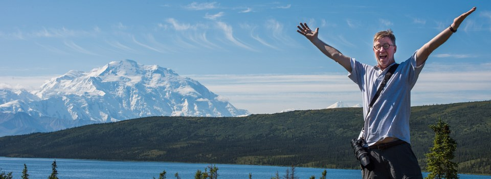 a man has his arms up with excitement, Denali is in the background