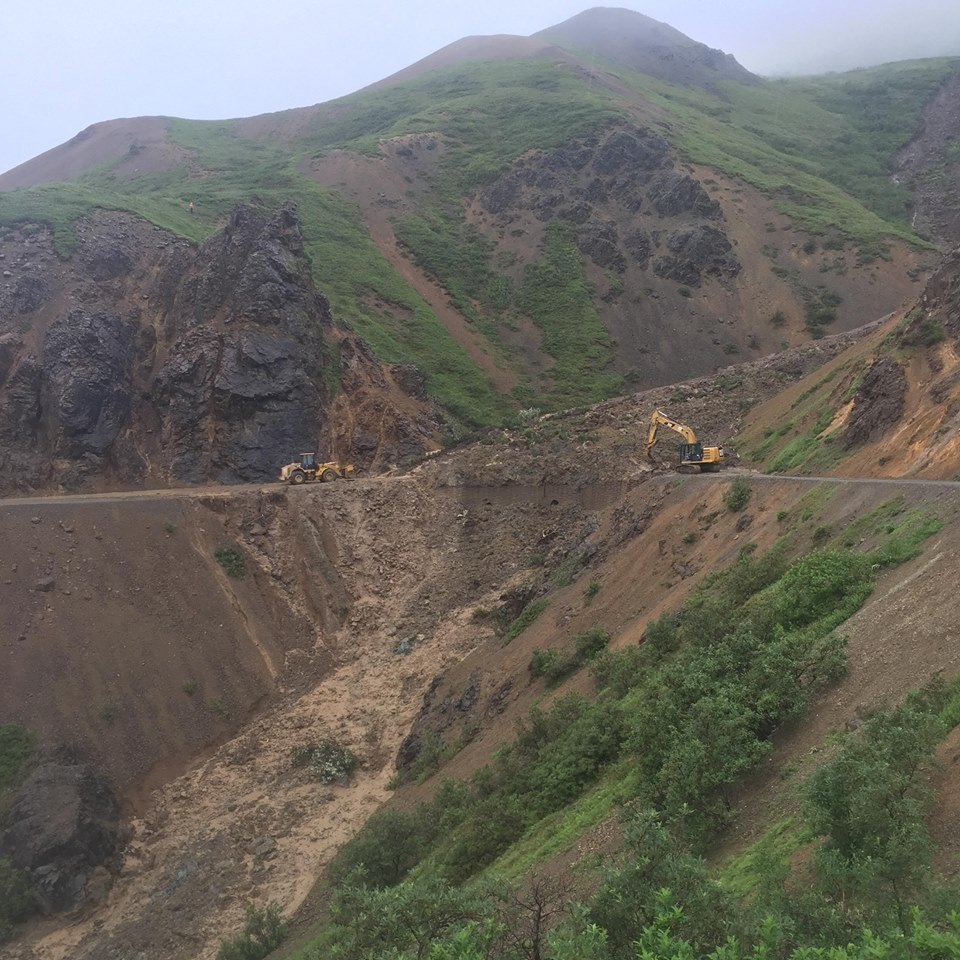 road equipment pushing a huge mud and rock slide off of a road on the side of a mountain