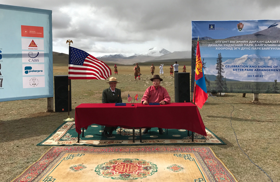 a park ranger and a man in traditional mongolian attire sit at a table outside in front of flags and posters