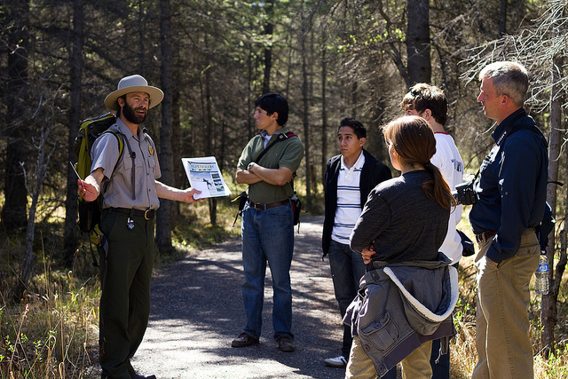 a ranger speaking to a group of people on a forested trail