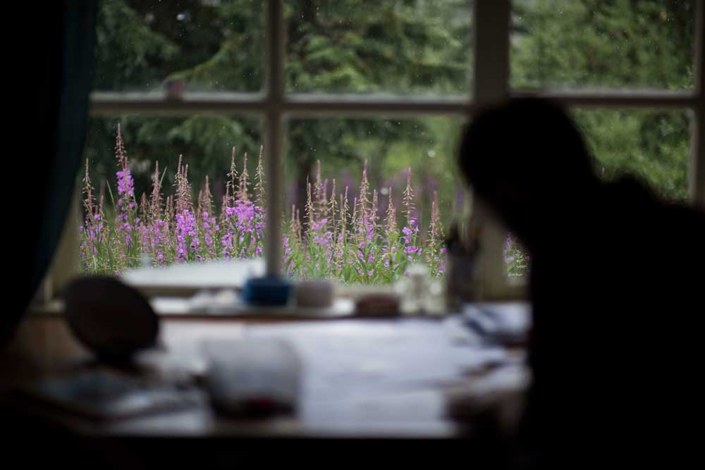 silhouette of a man drawing at a desk in front of a window with a view of pink flowers outside