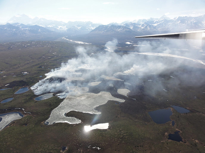 aerial image of distant mountains, tundra and smoke rising from wildfire