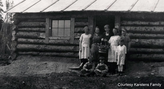 Historic image of family in front of a log cabin