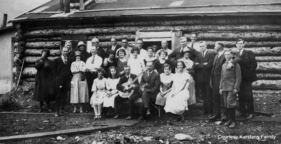 Historic photo of people in front of a cabin