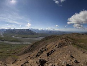 panoramic image from atop a ridge, looking at distant mountains