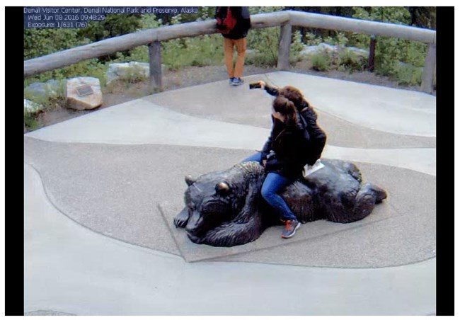 two people sitting on a bear sculpture taking a selfie