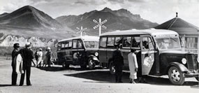 Historic black and white photo of park visitors and buses