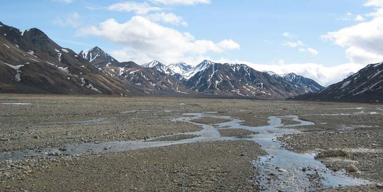 a wide, graveled plain leading up to brown, snow-dotted mountains