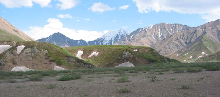 a gravel plain leading up to green hills, in front of taller, snow-dotted mountains
