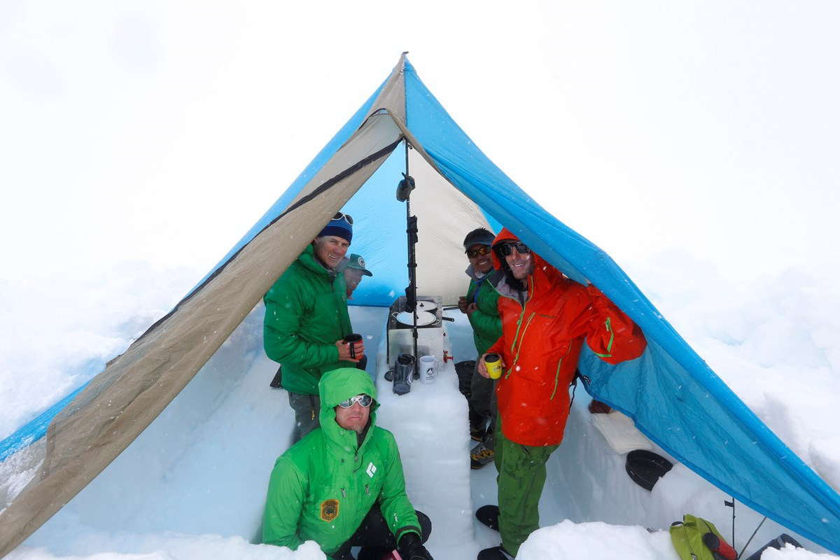 Climbers prepare a meal in a ventilated cook tent