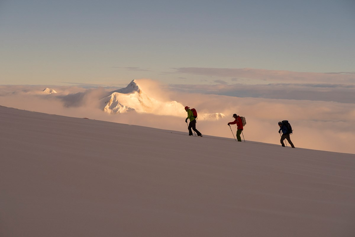 Mountaineers ascend a shadowy slope, with a glowing snowy peak in the distance