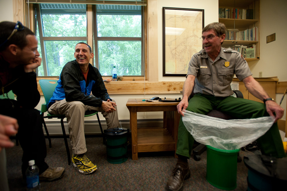 a ranger and two mountaineers sitting in a room, looking at a green plastic container