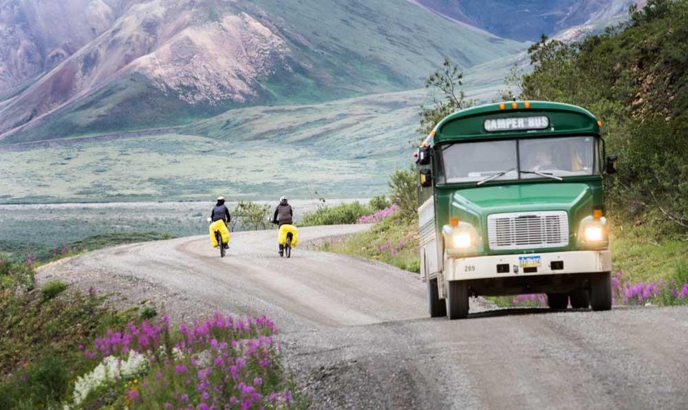 two people biking a dirt road past a green bus