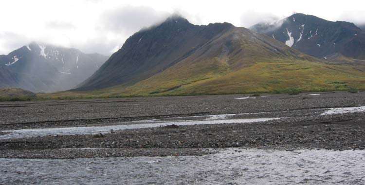 a river running through a rocky plain in front of cloud-shrouded mountains