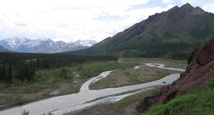 a river running through forest, past a tall mountain, other mountains in the distance
