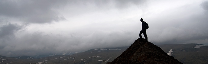 Silhouetted hiker on a rocky outcrop, misty skies and snow-dotted plain in the distance below.