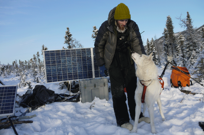 man bundled in winter clothing pets a sled dog near solar panels and other equipment in a snowy field