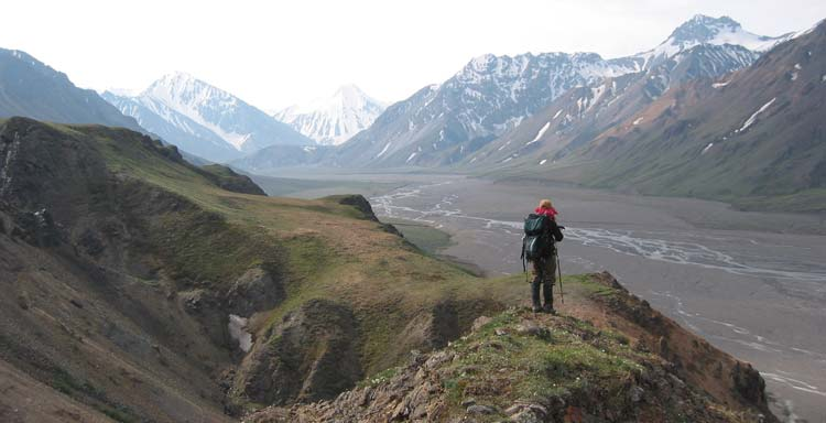 a hiker stands on a rocky ridge, overlooking a wide gravel river bed and distant mountains