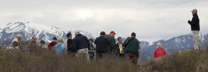 An Park Partner Interpreter speaks with a group of visitors to Denali, mountains are in the background.