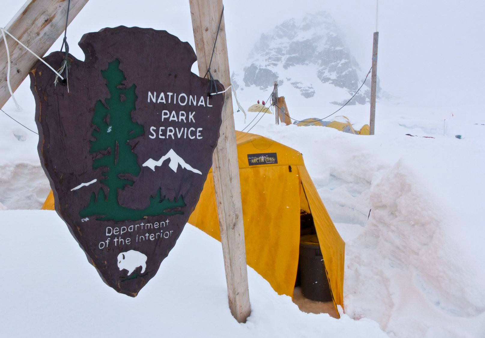 An NPS Arrowhead plaque demarks the location of the snowy ranger camp