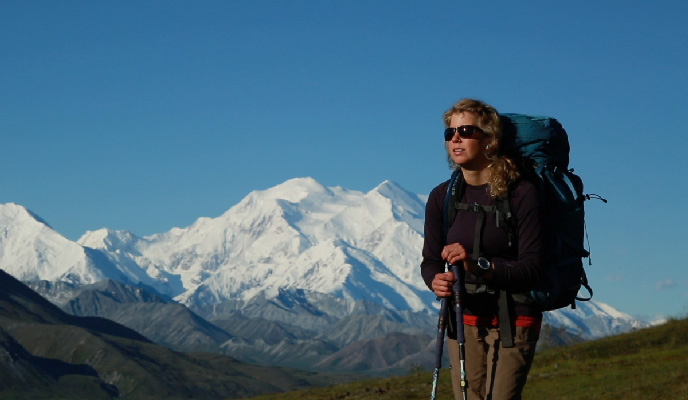 Woman wearing a backpack with vast snowy mountain in background
