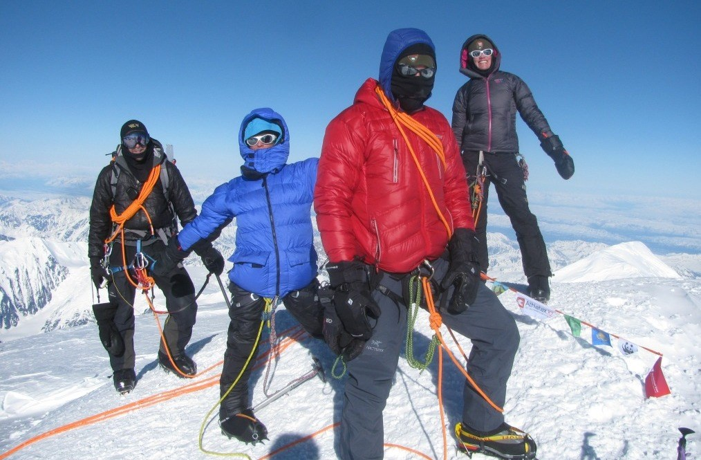 Climbers on summit wearing extreme cold weather gear