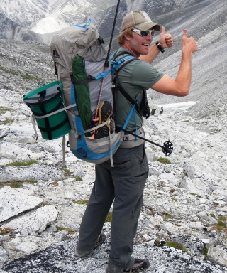 Climber carrying backpack with green CMC canister strapped to it.