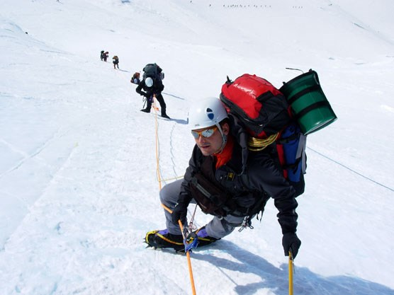 looking down a snowy slope at several mountain climbers, laden with equipment