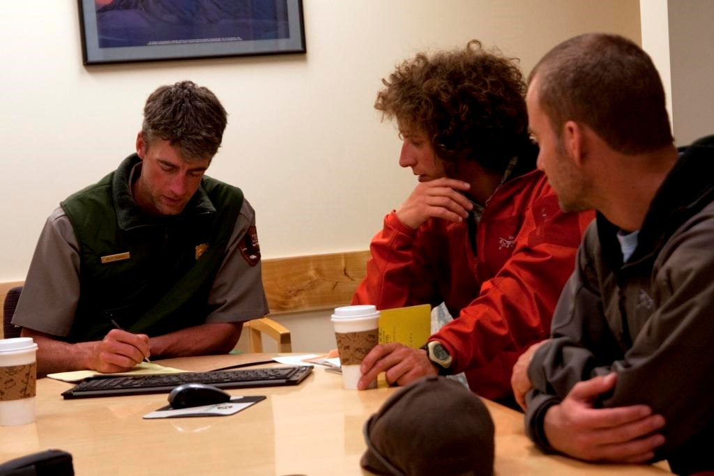 three men - two climbers and one ranger - sitting at a conference table