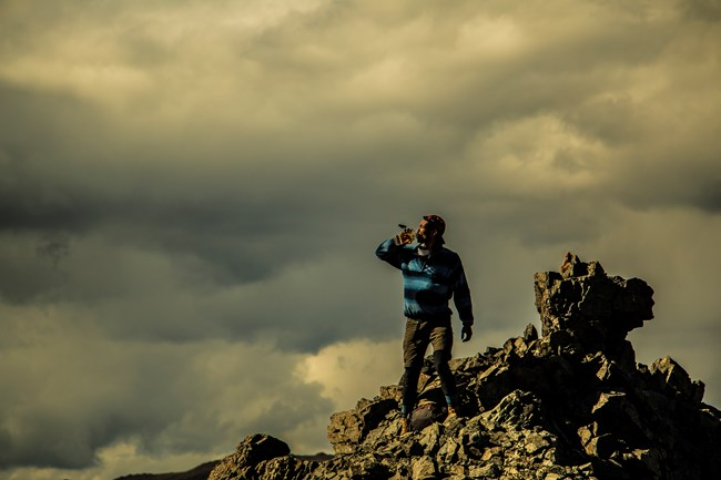 a man standing on a rocky outcropping atop a mountain
