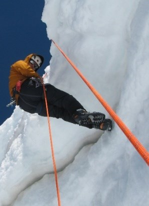 Climber rappelling down a rope into a crevasse