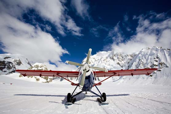 a small propeller plane sitting on a snowfield, with steep, snowy mountains in the background
