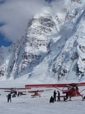 three prop planes on a snow field with a steep, snowy mountain behind