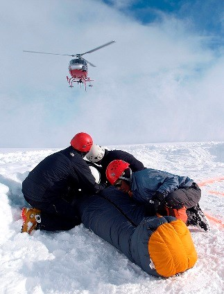 Climbers with a backboarded patient watching helicopter land