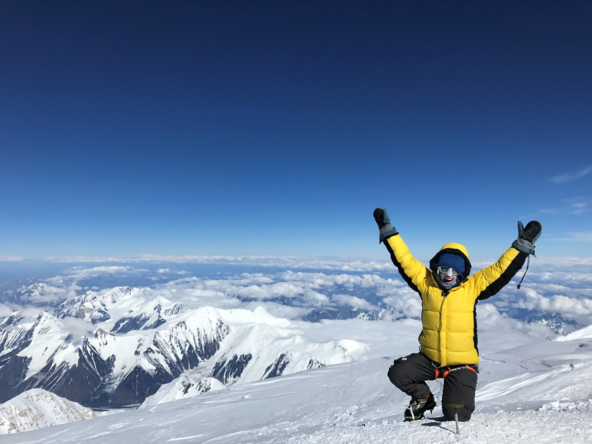 A happy and well-bundled climber celebrates on the summit
