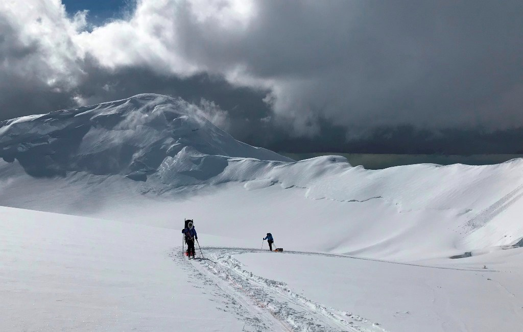 Two climbers ascend the mountain on skis under a dark cloudy sky