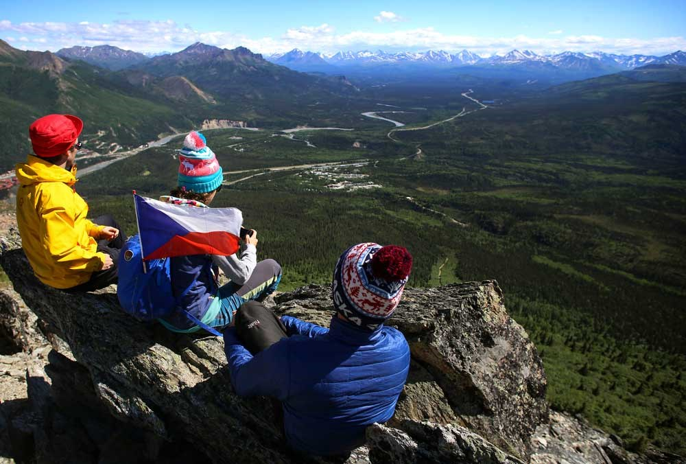 three people sitting on a rocky outcropping, looking out over a landscape of forests, mountains and roads