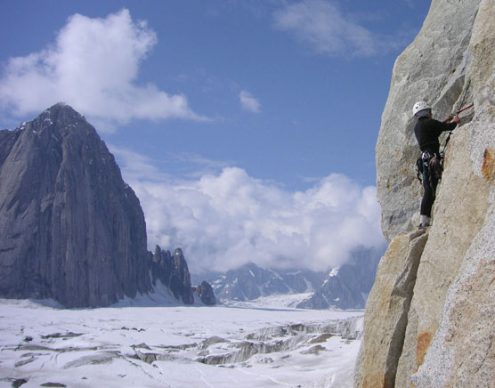 a person climbing on a nearly vertical spire of rock, overlooking a vast, crevassed glacier with other mountains in the distance