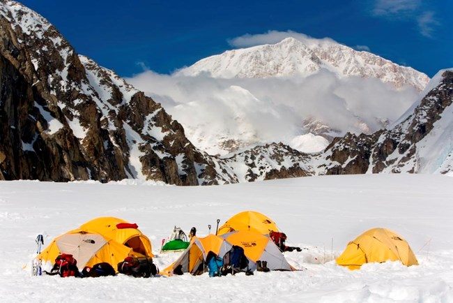 Expedition tents on glacier; snowy mountain in the distance