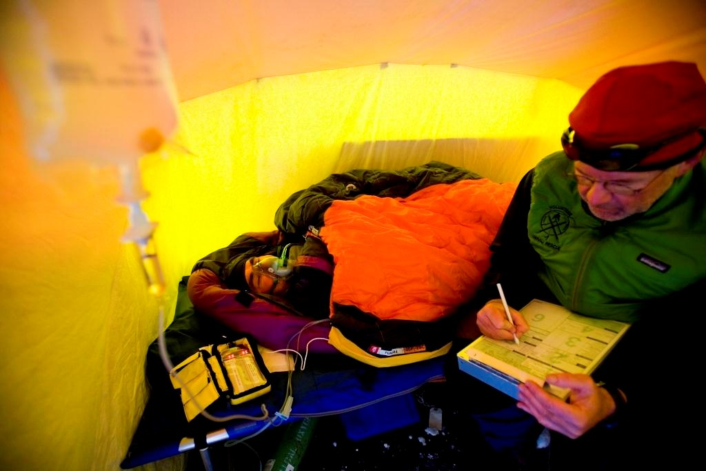 Physician seated in a tent next to a patient wearing anoxygen mask