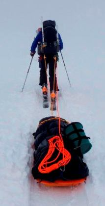 Climber towing heavy sled uphill