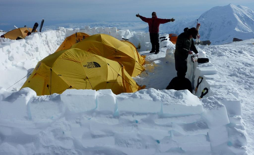 Tents and climbers enclosed by snow walls