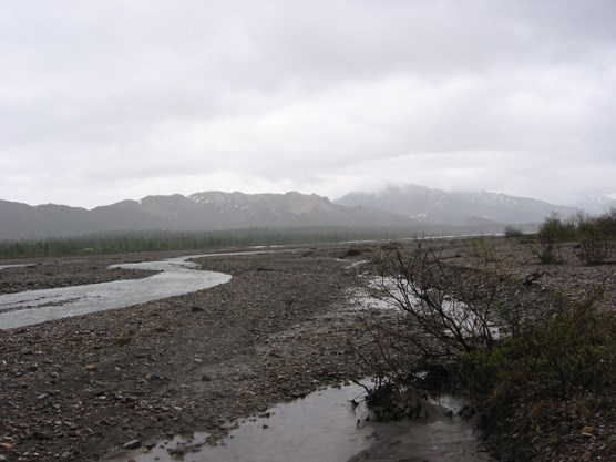 a wide gravel plain with a narrow river flowing through it, mist-shrouded mountains in the distance