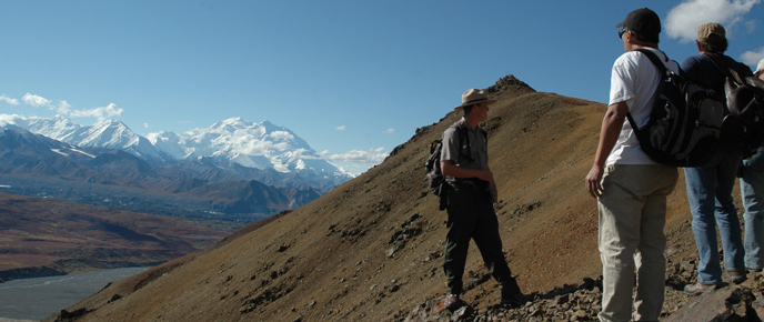 A ranger and hikers on an alpine ridge, Denali in the background