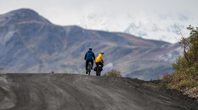two people biking on a dirt road, mountains in the distance
