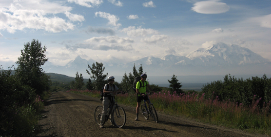two cyclists on a dirt road, an extremely large, white mountain in the background