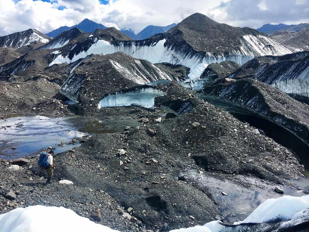 a glacial moraine covered in gravel, with patches of blue ice exposed