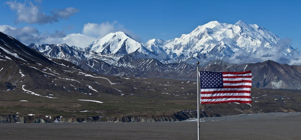 american flag flying in the foreground, snowy mountains in the distance