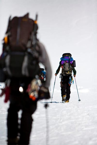 Two heavily-laden mountain climbers roped together, hiking on snow