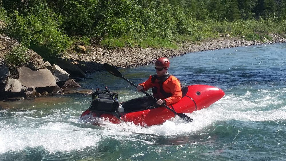 a man in a small red raft wearing a helmet and life jacket floats down a clear river